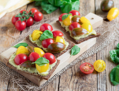 Bruschette di segale con hummus all'avocado e pomodorini colorati