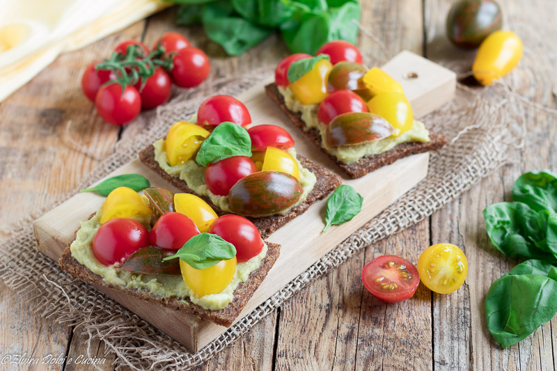 Bruschette di segale con hummus all'avocado e pomodorini colorati